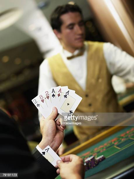 Young man holding playing cards and hiding an ace in his cuff