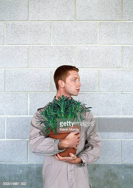 Young man holding pot plant in front of brick wall