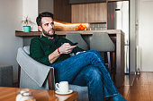 Young man holding remote controller watching tv