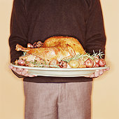 Young man holding roast turkey, mid section
