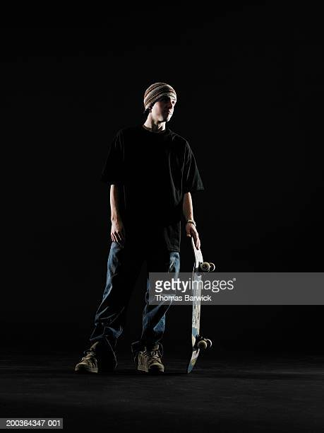 Young man holding skateboard, looking away