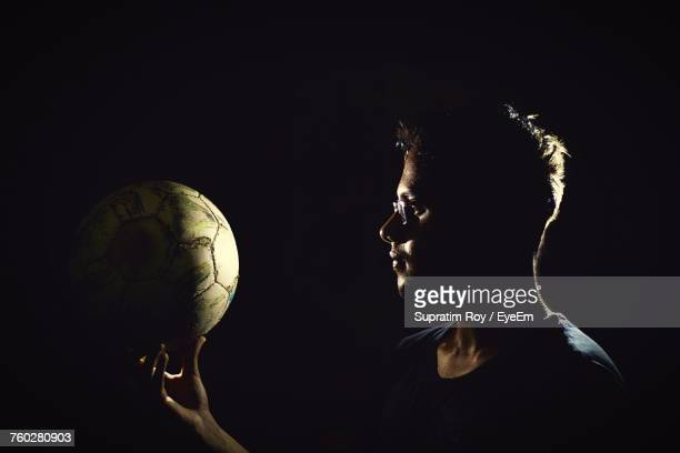 Young Man Holding Soccer Ball Against Black Background