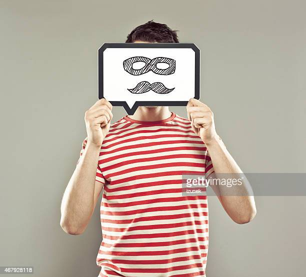 Young man holding speech bubble with mustache and mask