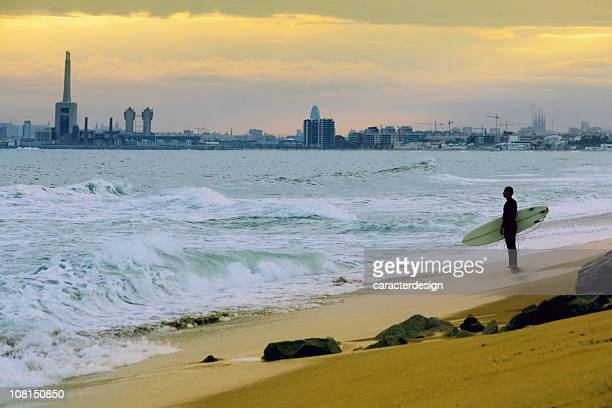 Young Man Holding Surfboard On Beach, Barcelona in Background
