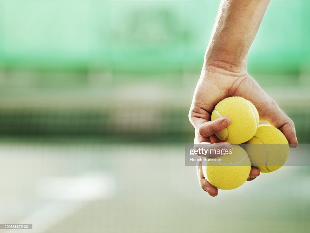 Young man holding three tennis balls in hand, close-up