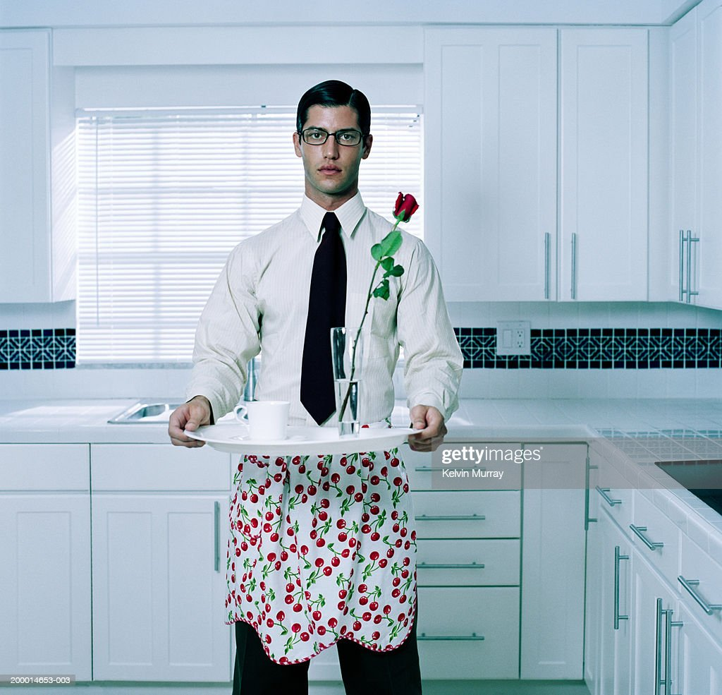 Young man holding tray in kitchen, portrait : Stock Photo