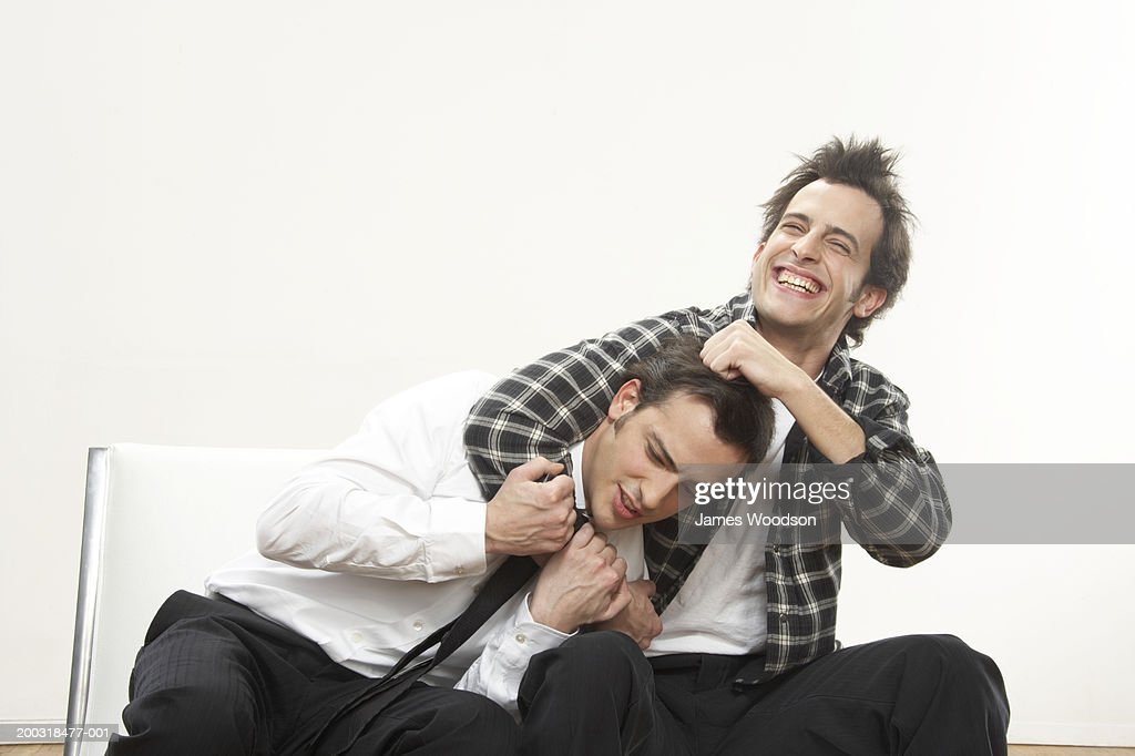 Young man holding twin brother in headlock, smiling : Stock Photo