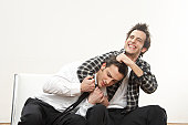 Young man holding twin brother in headlock, smiling