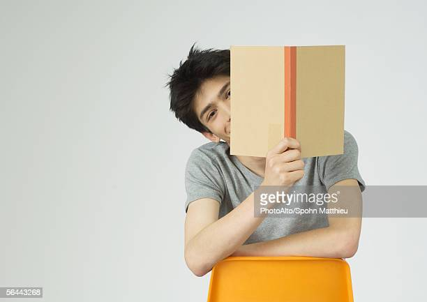 Young man holding up book, peeking around the edge of it