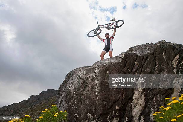 Young man holding up mountain bike on top of rock