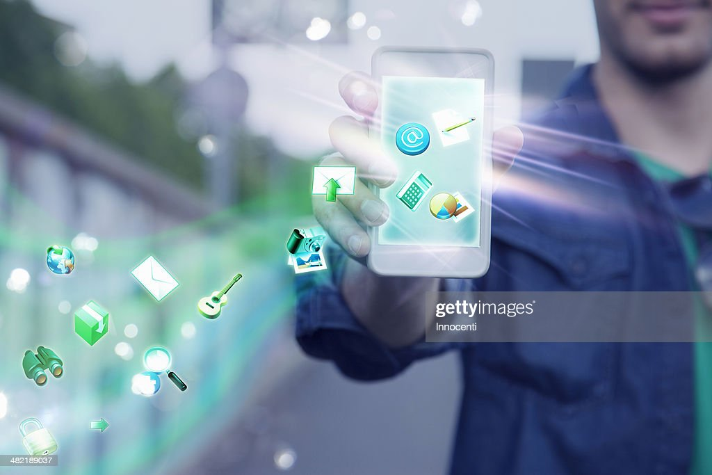 Young man holding up smartphone with apps and icons coming out of it : Stock Photo