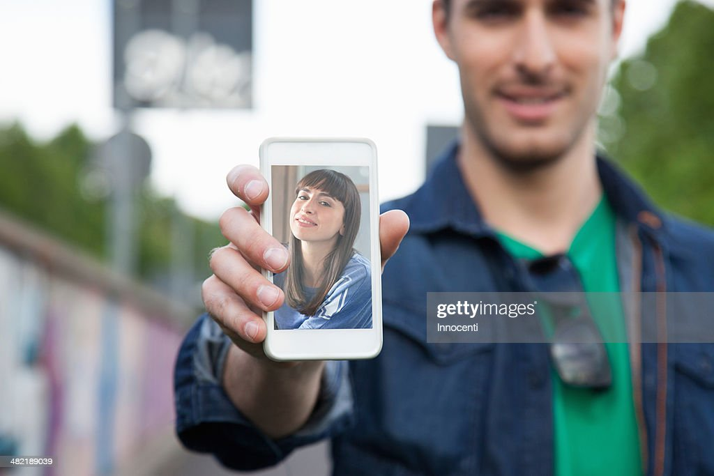 Young man holding up smartphone with photograph of girlfriend