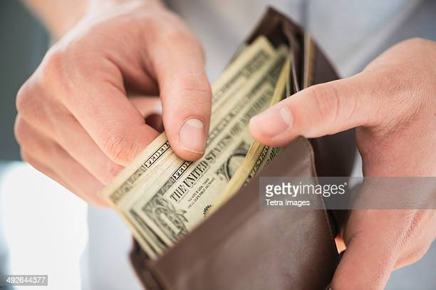 Young man holding wallet and counting money, Jersey City, New Jersey, USA