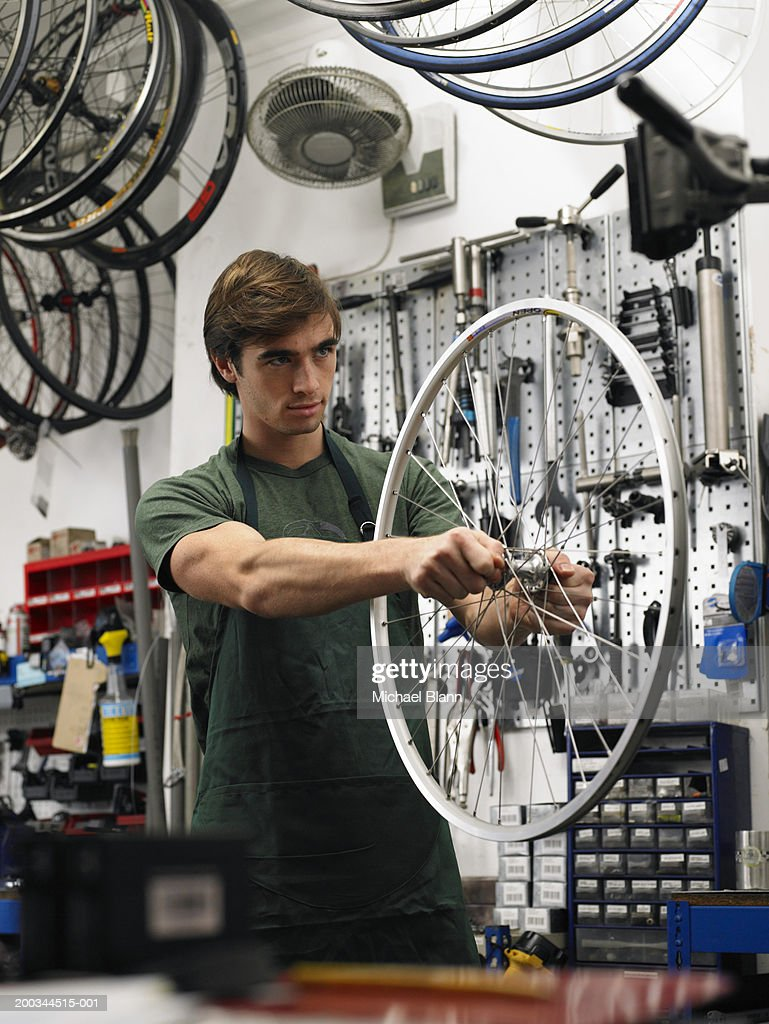 Young man holding wheel of bicycle in shop : Stock Photo