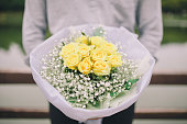 Young man holding white flower bouquet.