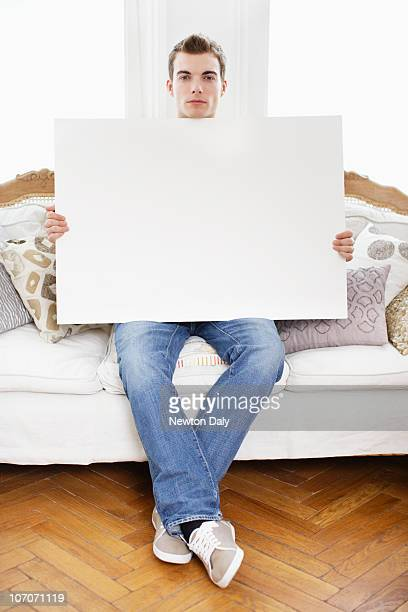 Young man holding whiteboard