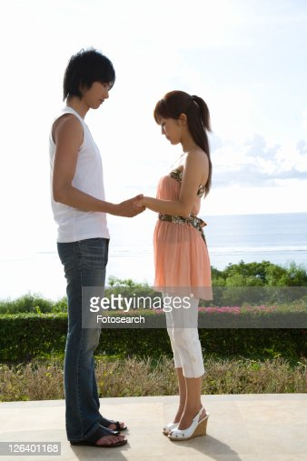 Young man holding woman's hands, standing face to face, Saipan, USA