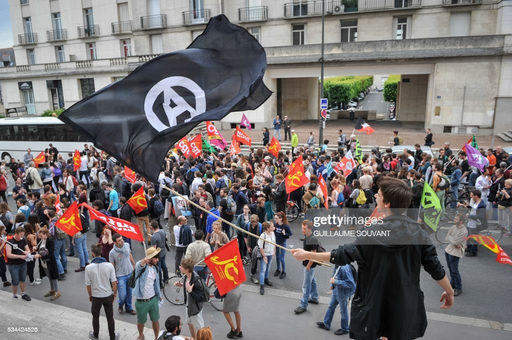 A young man holds a black flag with the anarchist symbol during a protest against the government's planned labour law reforms on May 26, 2016 in Tours, Central France. The French government's labour market proposals, which are designed to make it easier for companies to hire and fire, have sparked a series of nationwide protests and strikes over the past three months. The sign reads 'Our rights are on holidays in Panama'. / AFP / GUILLAUME