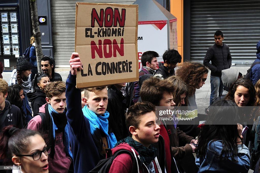 A young man holds a placard reading 'No to El Khomri, no to bullshit' as he demonstrates in the streets of Marseille during the traditional May Day rally on May 1, 2016. / AFP / Franck PENNANT