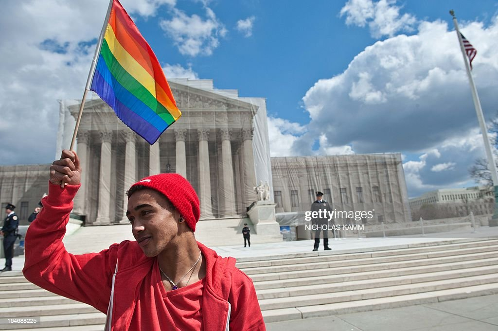 A young man holds a rainbow flag in front of the US Supreme Court in Washington on March 26, 2013 as the court hears arguments on California's Proposition 8 ban on same-sex marriage. AFP PHOTO/Nicholas KAMM