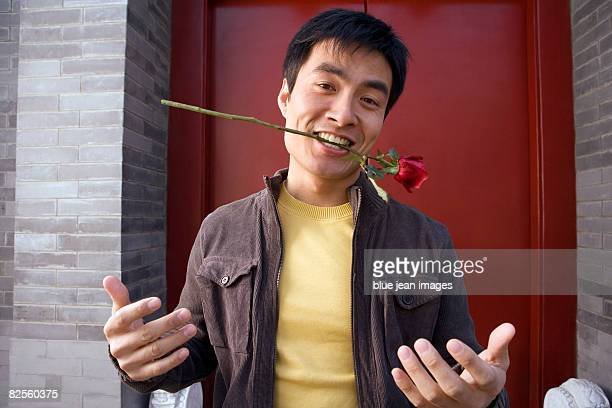 A young man holds a rose in his teeth.