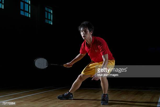 Young man holds his badminton racket and moves from side to side during a game of badminton.