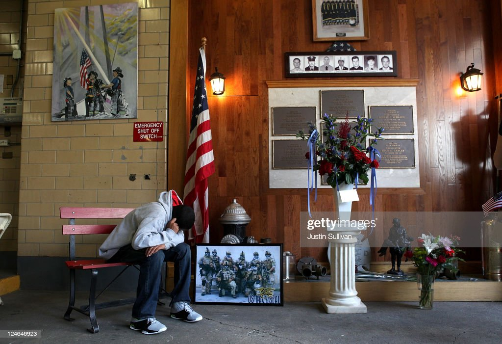 A young man holds his head as he sits in front of a memorial for FDNY firefighters from Ladder Company 20 that died at the World Trade Center during September 11 terror attacks before a ceremony to mark the 10th anniversary of the 9/11 attacks on September 11, 2011 in New York City. New York City firefighters are commemorating the 10th anniversary of the 9/11 terrorist attacks and honoring the 343 firefighters who died in the line of duty.