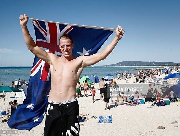 A young man holds the Australian flag above his head during Australia Day celebrations January 26 2007 in Rye Australia Australians all over the...