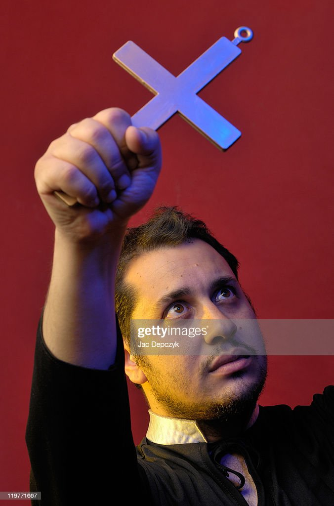 Young man holds up crucifix, red background.