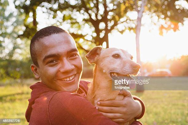 young man hug his small Mixed-breed dog, looking at camera
