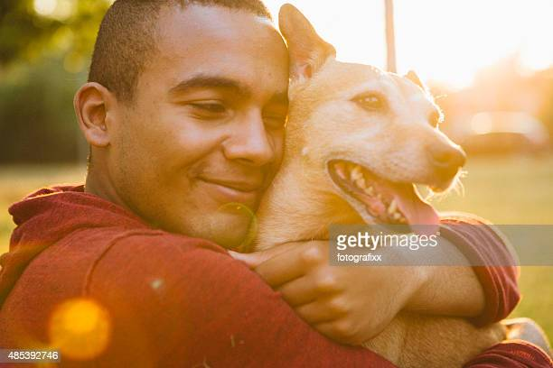 young man hug his small Mixed-breed dog