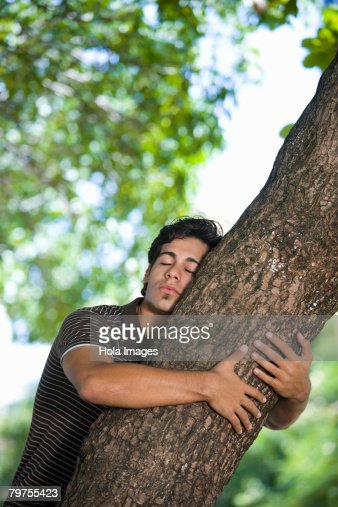 Young man hugging a tree trunk : Stock Photo