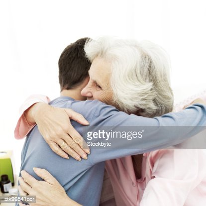 young man hugging an elderly woman : Stock Photo