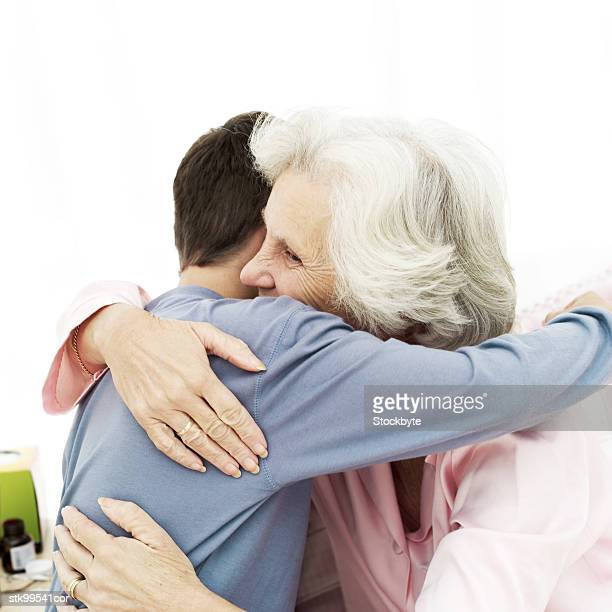 young man hugging an elderly woman