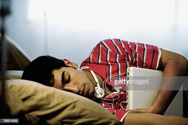 Young Man Hugging Laptop in Sleep