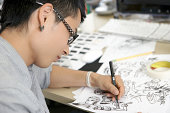 Young man illustrating comics at his desk