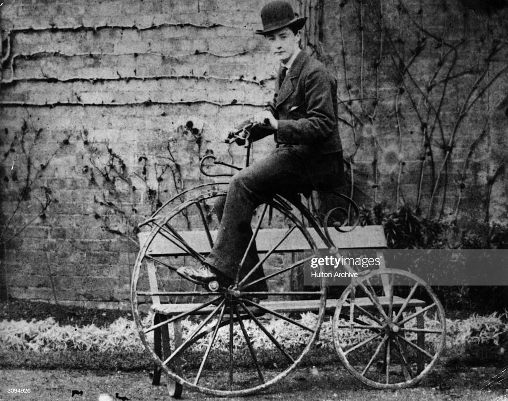 A young man in a bowler hat sits on a penny-farthing known as an 'Ariel', with his foot on a convenient bench.