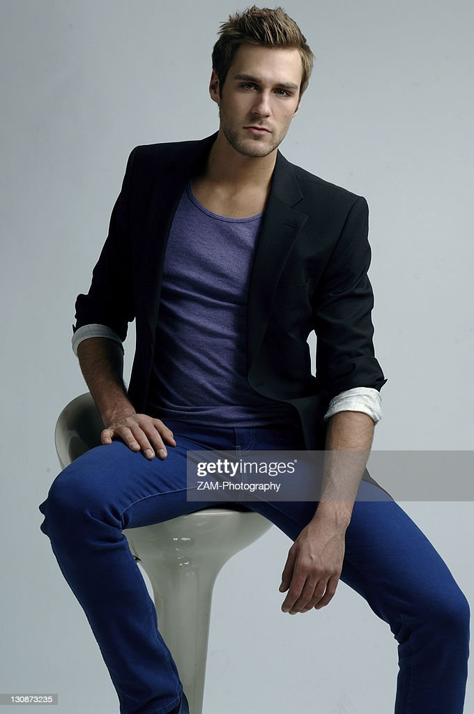 Young man in a jacket sitting on a stool, fashion shoot : Stock Photo