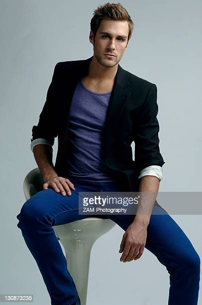 Young man in a jacket sitting on a stool, fashion shoot