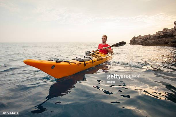 若い男性の海でのカヤック