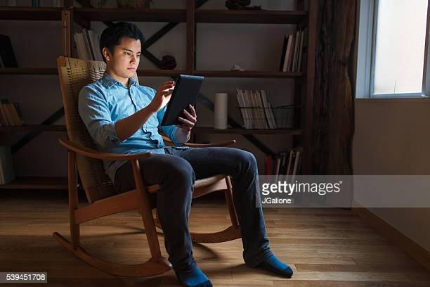 若い男性のロッキングチェアをデジタルタブレット
