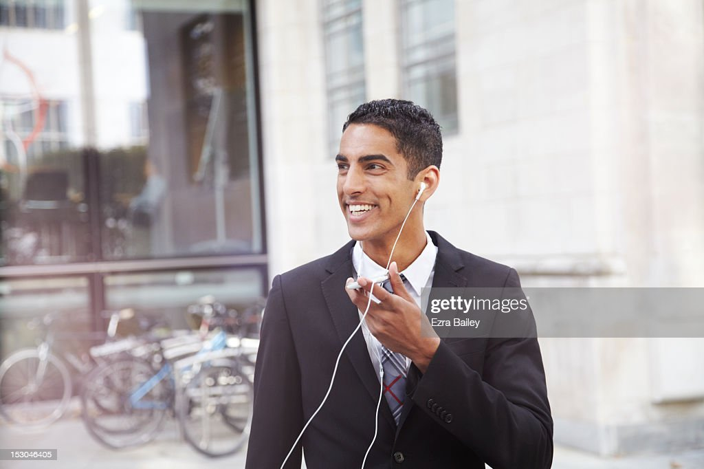 Young man in a suit talking into mobile phone. : Stock Photo