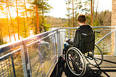 Young lonely man in a wheelchair on a balcony looking at the nature in the spring