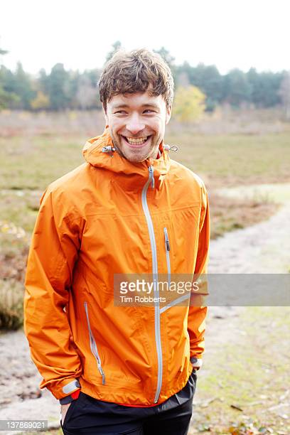 Young man in all weather coat smiling.