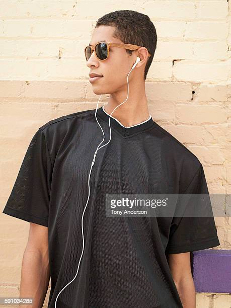 Young man in alley with ear buds and sun glasses