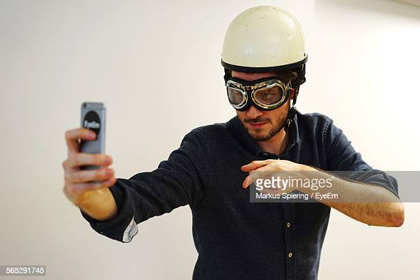 Young Man In Aviator Glasses And Helmet Taking Selfie Against White Wall