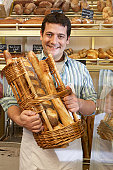 Young man in bakery, holding basket of baguettes, smiling, portrait