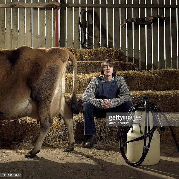 Young man in barn by cow and milking equipment, portrait