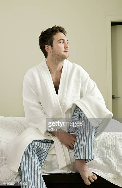 Young man in bathrobe sitting on bed