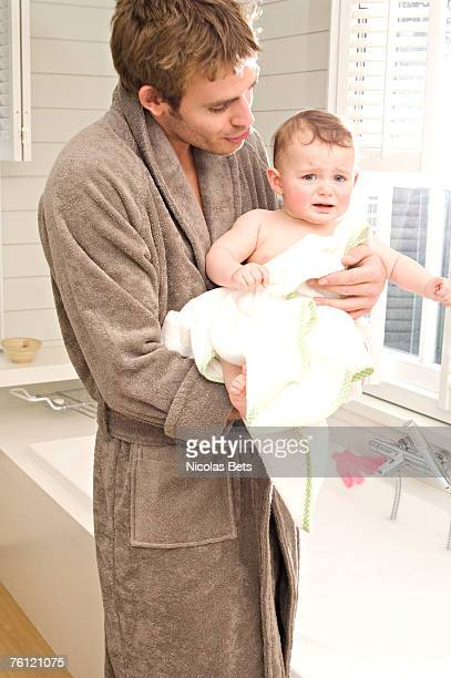Young man in bathrobe with baby in bathroom